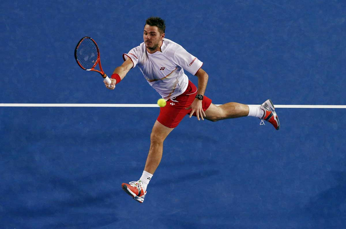 Stanislas Wawrinka of Switzerland hits a return to Novak Djokovic of Serbia during their men's singles quarter-final tennis match at the Australian Open 2014 tennis tournament in Melbourne