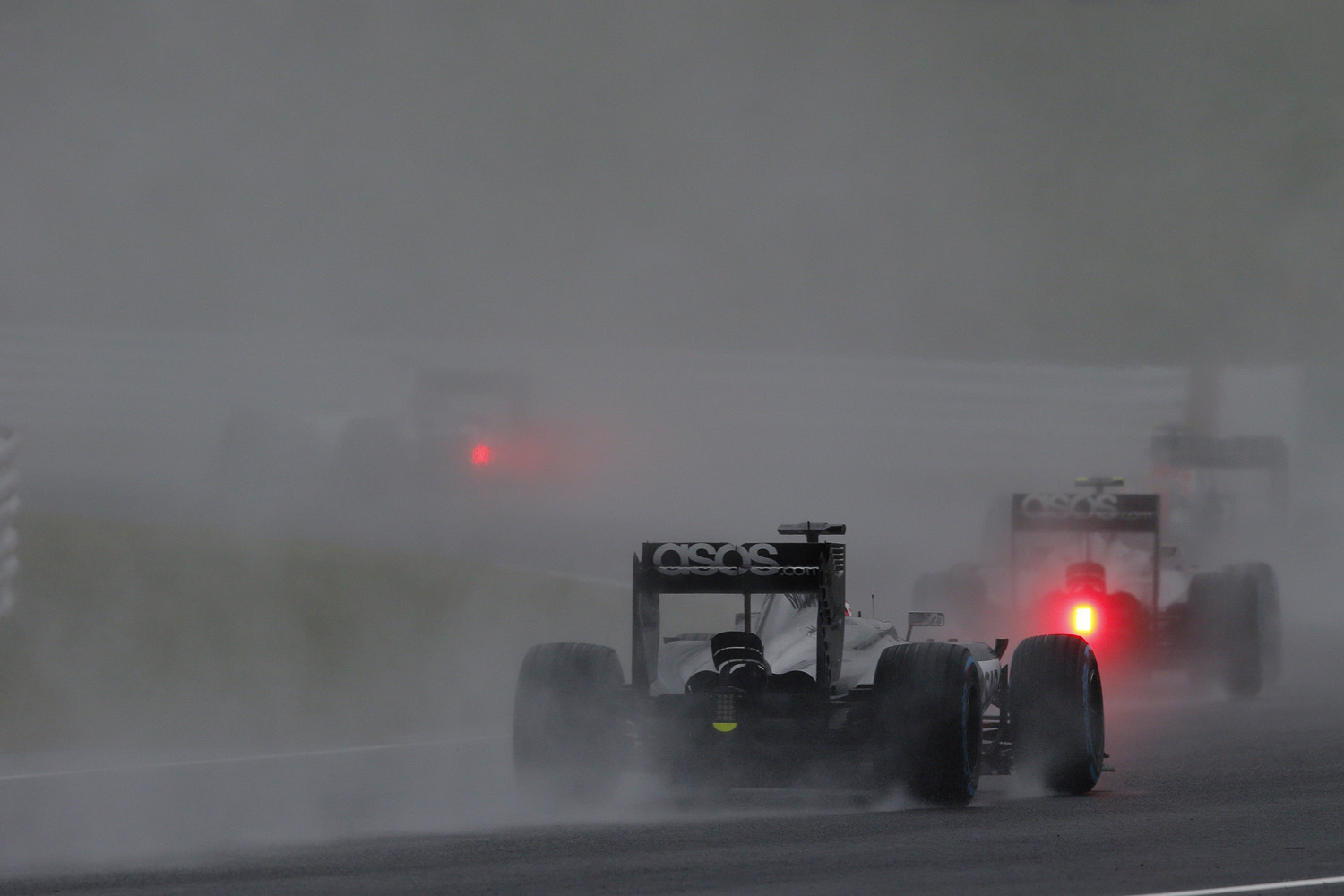 Kevin Magnussen and Jenson Button on track.